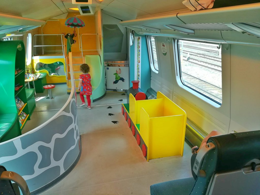 A girl is playing in a playroom on a train